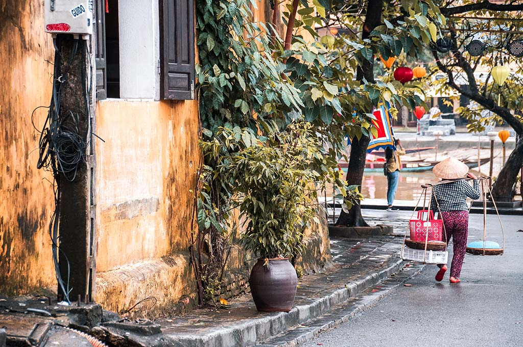 woman with a Vietnamese hat walking on the street of Hoi An, green plants and orange wall, awesome trip from Da Nang