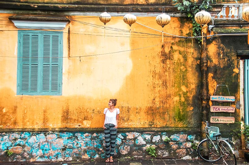 a woman standing in front of the yellow wall with yellow lanterns and blue window in Hoi An, perfect trip from Da Nang.