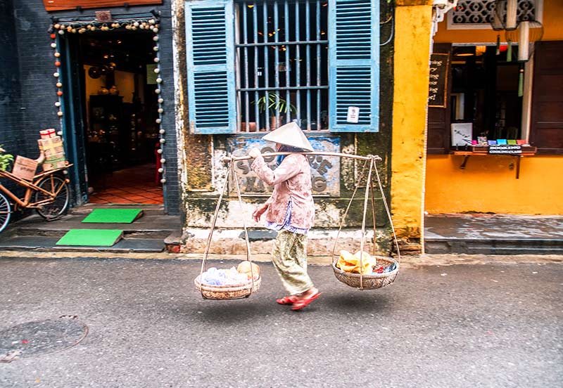 a Vietnamese woman with a bamboo hat carrying a two baskets in Hoi An, perfect trip from Da Nang.