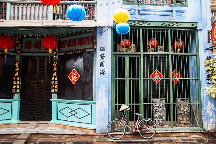 a blue walls with colourful Chinese lanterns and Chinese signs and a bicycle with a Vietnamese hat.