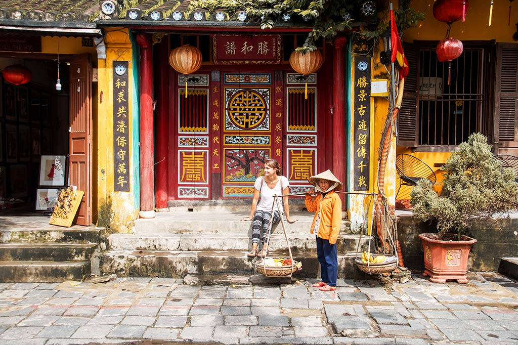 Chinese red temple, with girl sitting on the steps with Vietnamese lady in Hoi An, Vietnam