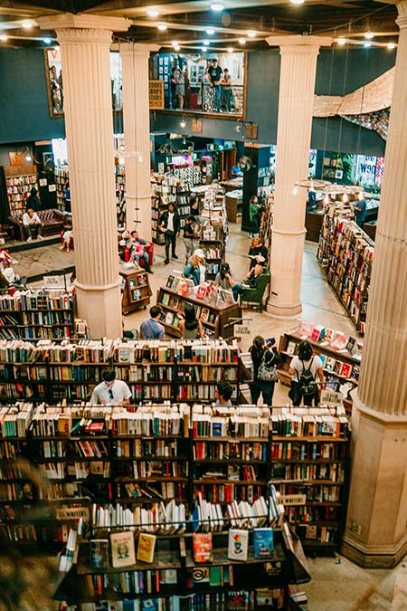 many book shelves and people in the last book store