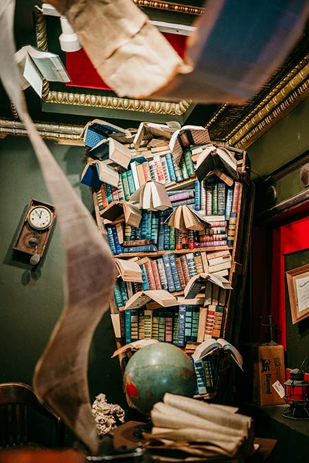 books on the shelves with green globus and clock
