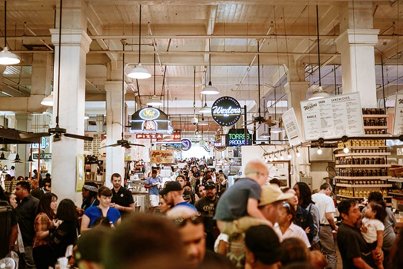 many people in the  Grand Central market, with many food signs which is one of the best things to do in downtown Los Angeles