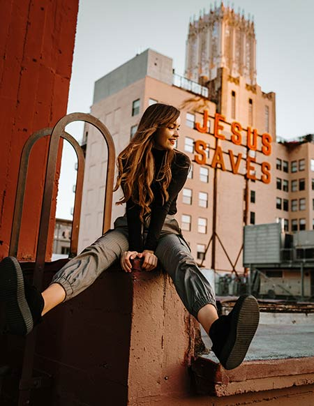 woman sitting on the grey pillar in front of a red sign Jesus saves in downtown LA