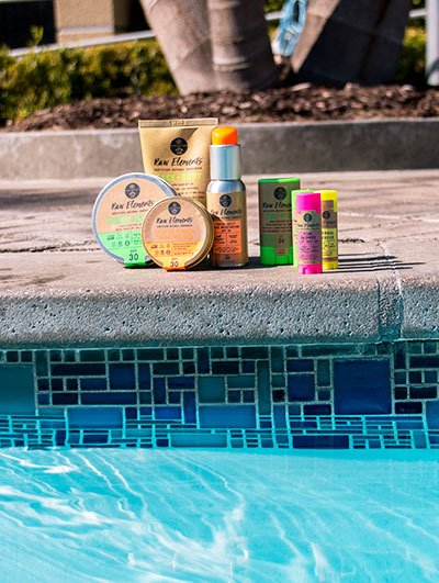 sun lotions from Raw elements next to a pool
