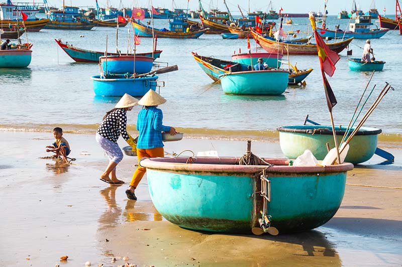 blue boats on the beach with two Vietnamese locals and one boy playing in the sand