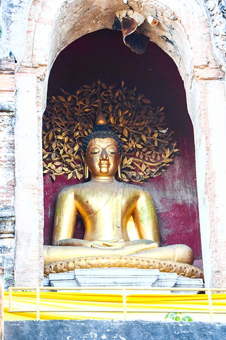 golden statue of Buddha with a purple wall and golden tree