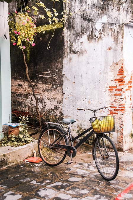 black bicycle standing in front of the white wall with orange bricks and yellow bag in the basket in Hoi An, perfect trip from Da Nang
