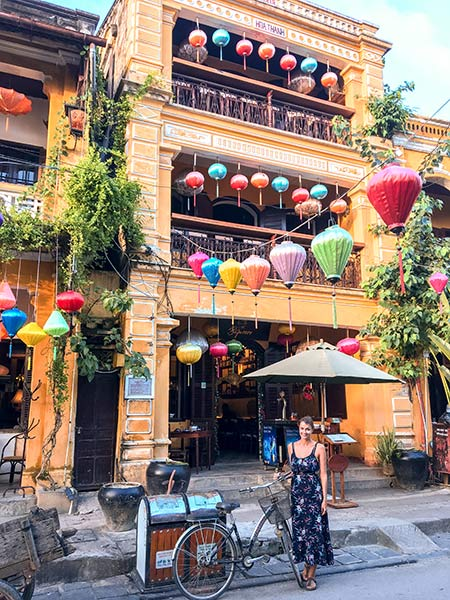 woman standing in fron of the orange wall full of colourful lanterns in Hoi An.