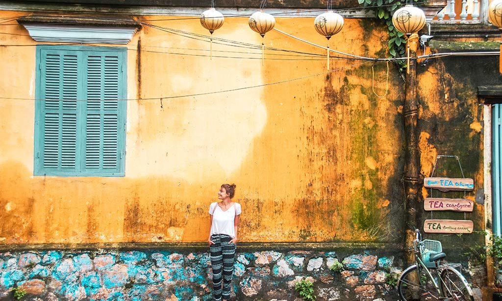 best things to do in Hoi An, Vietnam, yellow wall, blue window and a girl standing