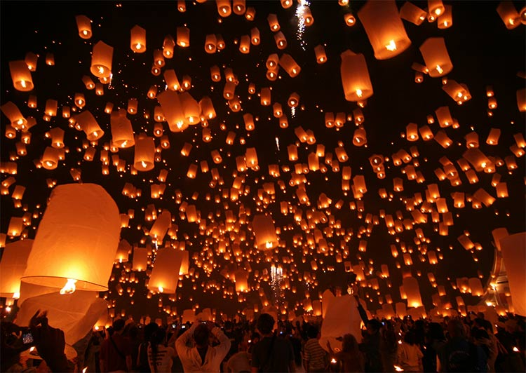 many lit lanterns in the air at night during Chiang Mai lantern festival