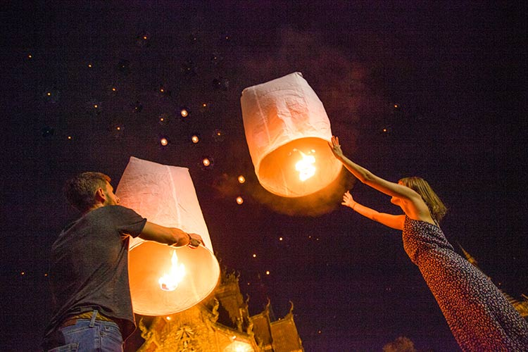 two people holding lit orange lanterns during the Yee Peng festival which has to be in your Chiang Mai itinerary.