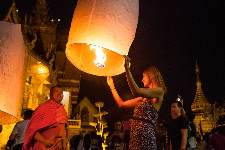 woman holding a lit lantern and a monk standing next to her during Chiang Mai's magic lantern festival which has to be in your itinerary.