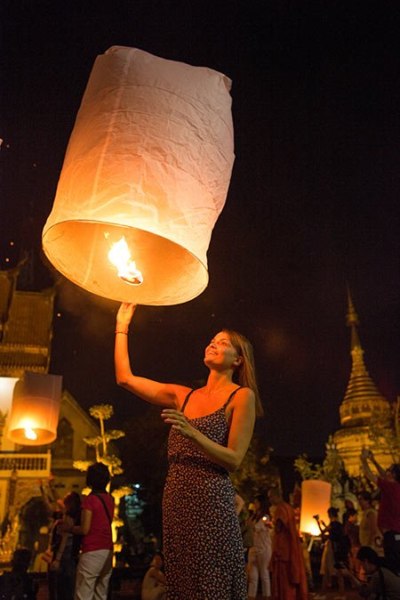 woman in a dress holding in a hand lid lantern in Chiang Mai
