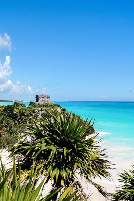 a view on Mayan ruins of Tulum, Caribbean blue water and green palm trees, Mexico