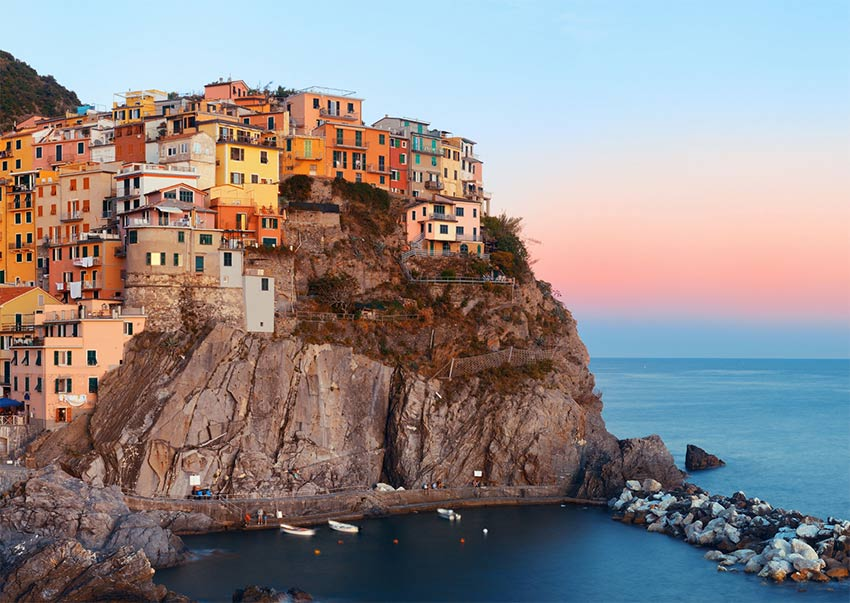 a view on pink sky, colourful houses on the cliff in Cinque Terre in Italy, one of the prettiest bucket list places in the world