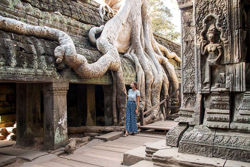 woman in the blue skirt standing in front of the tree on the roos in Angkor Wat in Cambodia which needs to be in your bucket list of awesome places