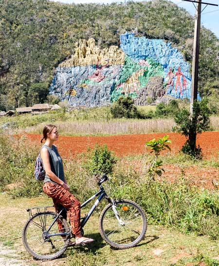 a girl in a orange pants sitting on the bicycle in from of the colourful mural in Vinales, Cuba