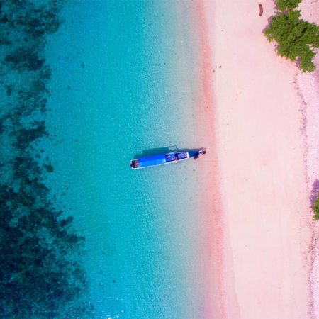 an arial view on the pink beach in Indonesia near Labuan Bajo, with a boat and turquoise water