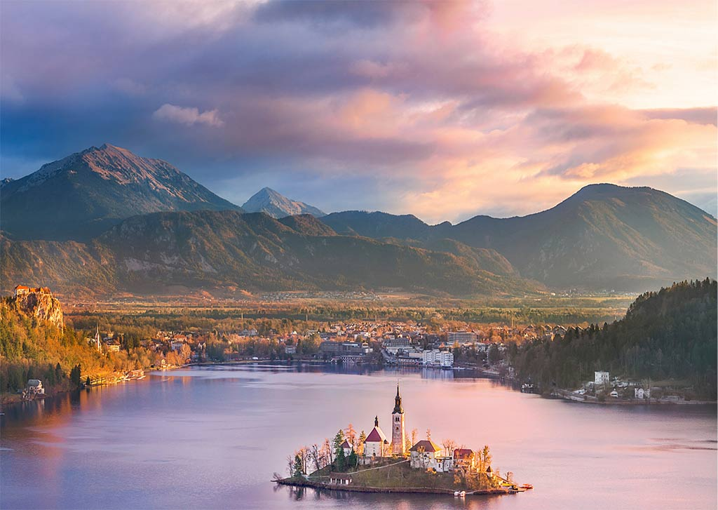 a view on pin sky, mountains and the lake Bled which is one of the beautiful bucket list places