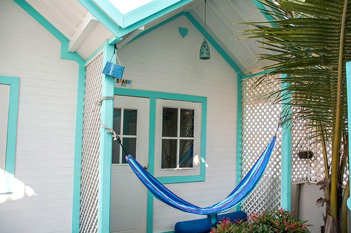 white house with blue frame and blue hammock