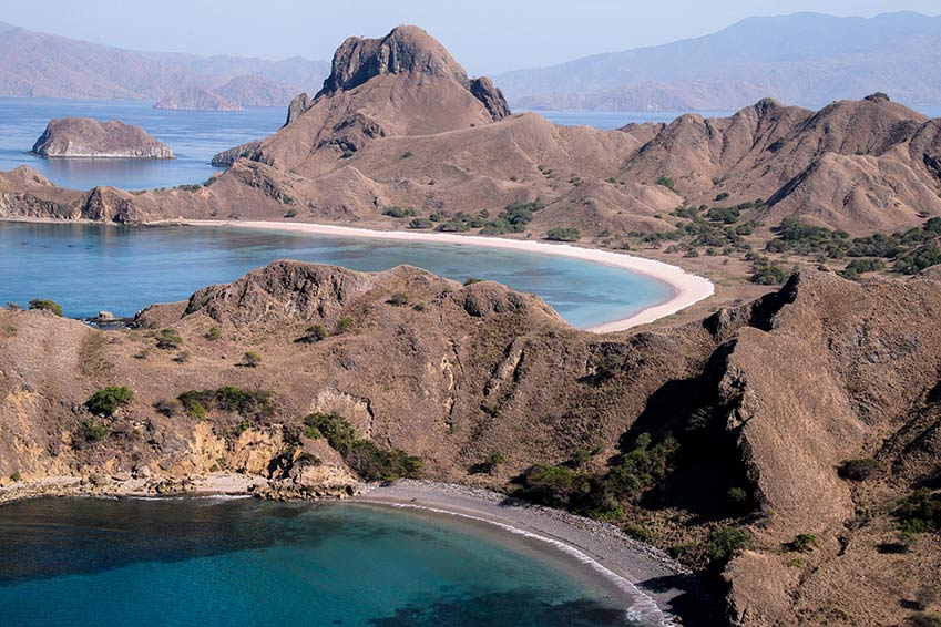 a view on pin and black sand beach from the cliff on Padar Island