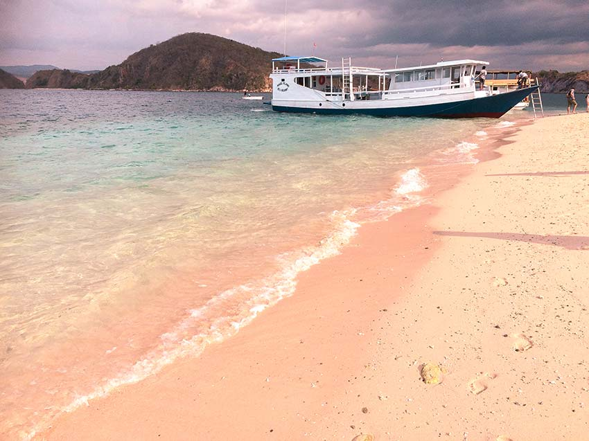 a view on the pink beach, mountains and the boat on Bidadari Island