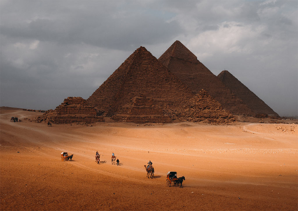 brown photo with pyramids of Giza in Egypt and camels, one of the dreamy bucket list places  that you need to visit