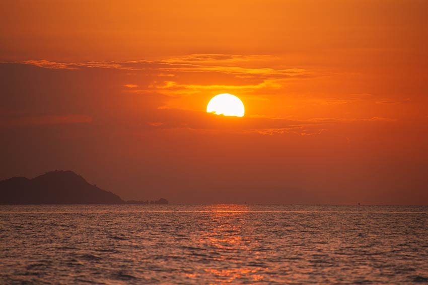 orange sky with the sun setting down over the sea
