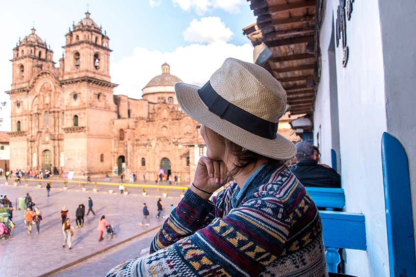 woman with a white hat looking out with a view on the red church in plaza de armas, which is the best area to stay in Cusco