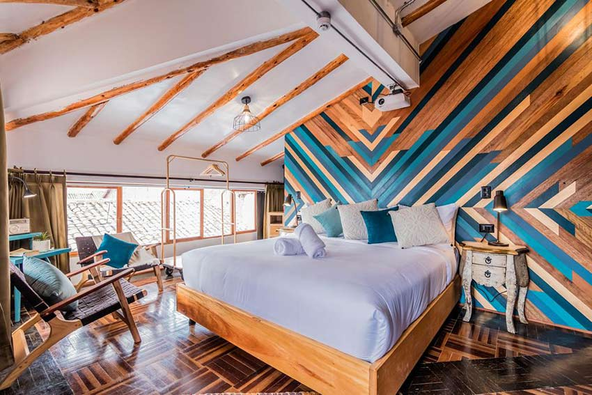 cute bedroom with wooden pillars in Selina Hotel, one of the best places to stay in Cusco