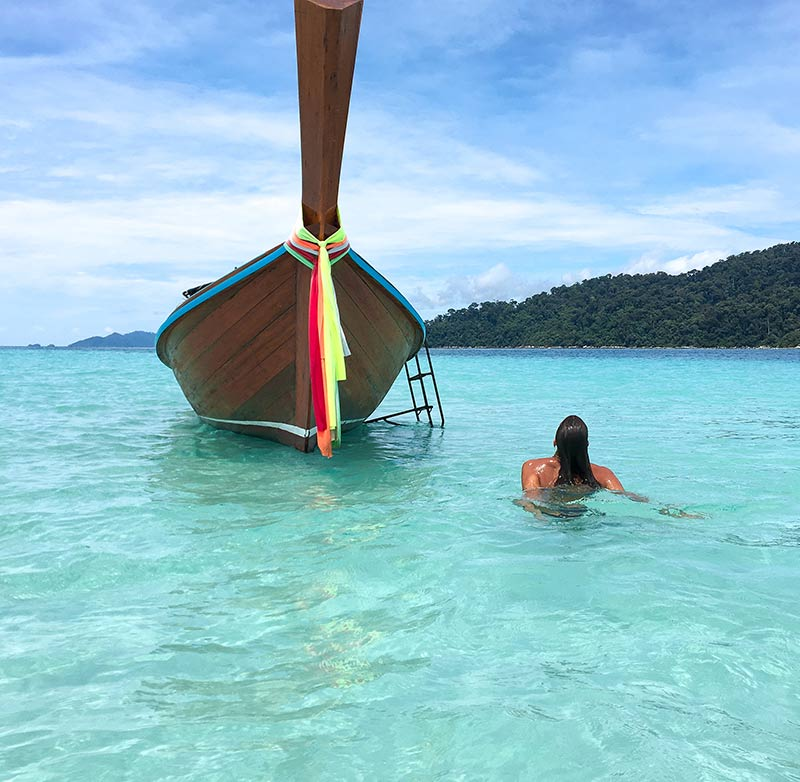 woman swimming in the turquoise waters and in front of Thai boat on Koh Lipe