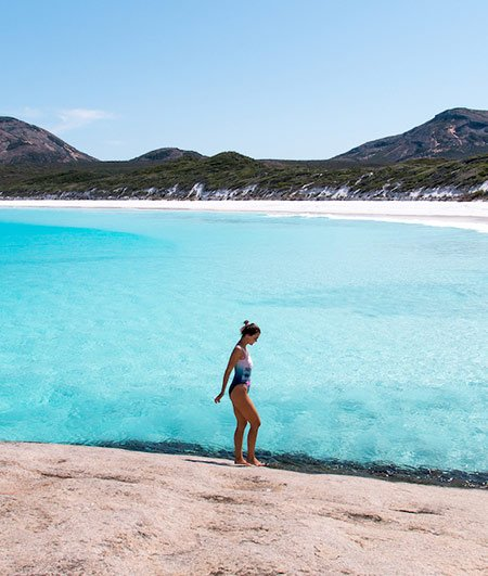 girl in the swimsuit standing on the rocky ground with blue water at Hellfire Bay, Esperance