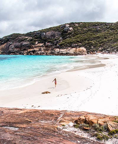 a woman running on the white sand beach, blue water and green hills in Esperance, Cape Le Grand, Australia