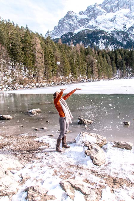 a girl in an orange sweater throws snow in the air with a lake and trees in the background