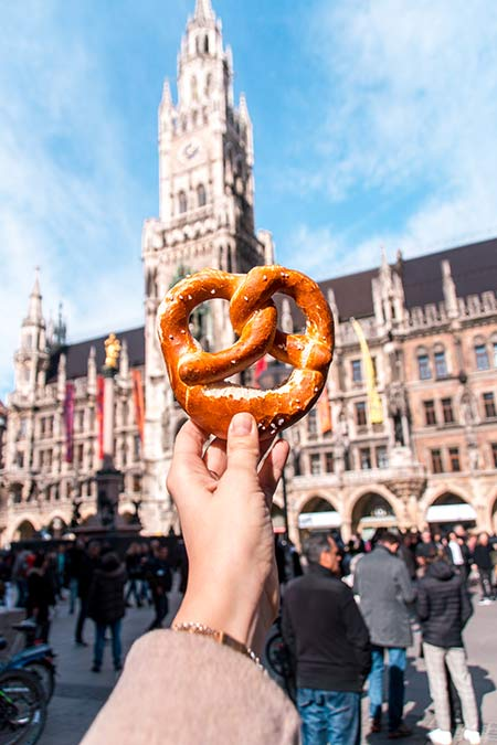 a hand holding up a brezel with the new townhall of Munich in the background