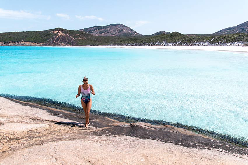 woman in a swimwear running on the rocky ground, turquoise water in Esperance, Western Australia