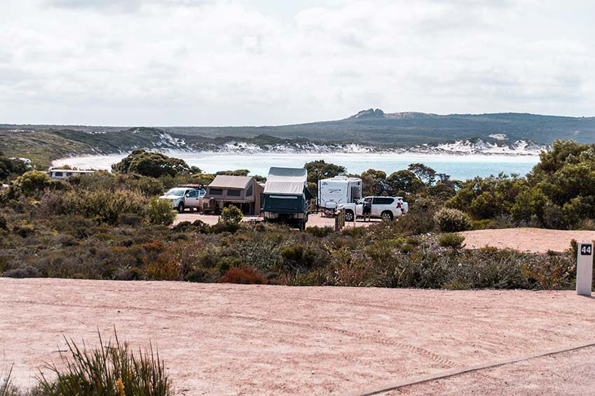 a view on several camping vans, green bush and Lucky bay beach