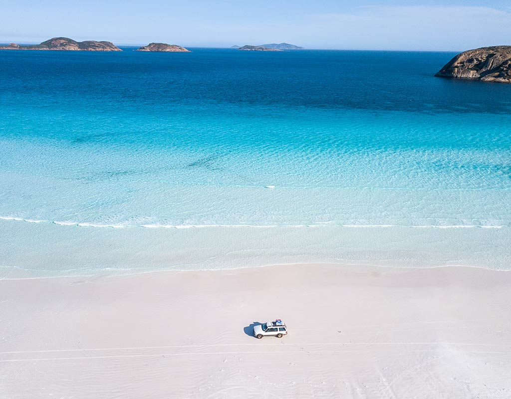 white car driving on the white sand beach in Lucky bay, Esperance with blue water