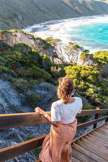 woman in brown skirt looking out at the ocean standing on the brown staircase, blue water and green bush in Esperance