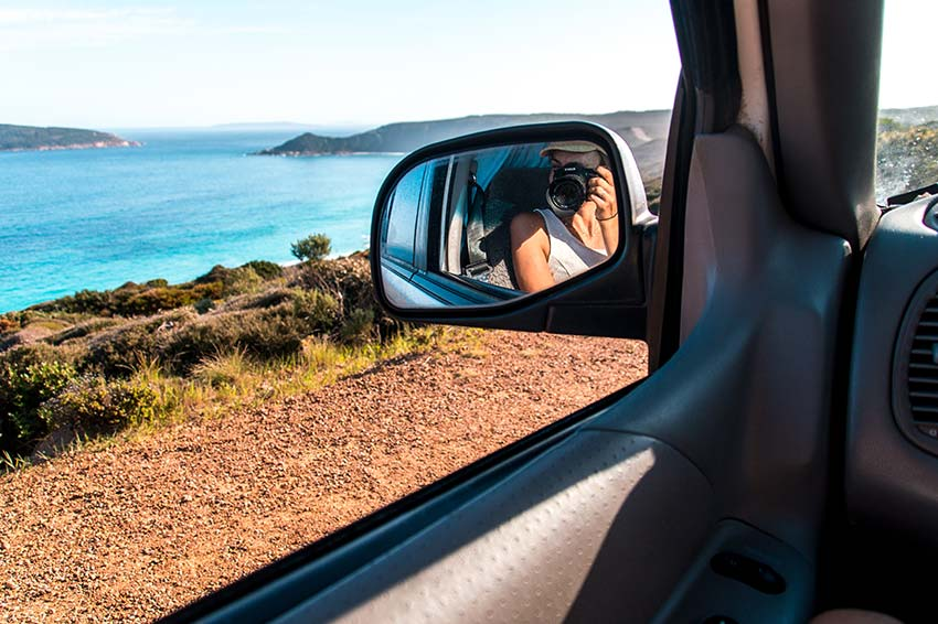 woman taking a photo in the car of the coastline