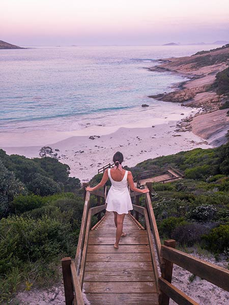 girl in a white dress standing on the wooden staircase with a view on the ocean and pinky sky