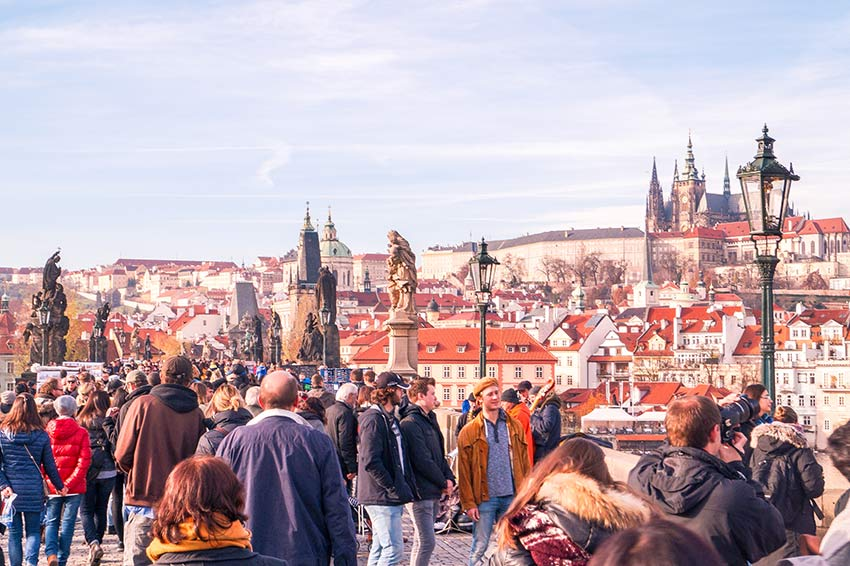 many people walking on the Charles bridge that is one of the most beautiful photo spots in Prague