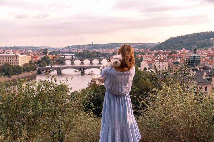woman in a blue dress holding a white day looking at the view of prague from Letna Hill which is one of the best photography spots in Prague