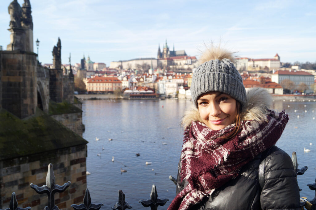woman in a grey hat, purple scarf standing in front of the Prague castle, one of the best photo spot
