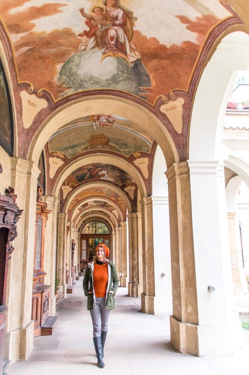 woman in orange sweater walking among colourful pillar and colourful ceiling.