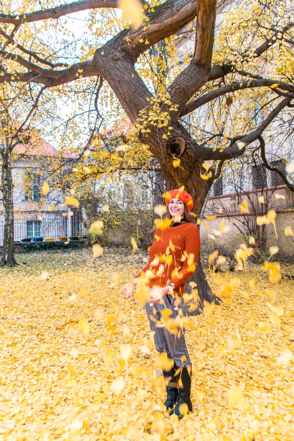 woman in orange sweater and hat throwing orange leaves in Prague