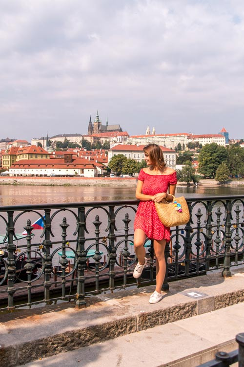 woman in a red dress standing net to the black rain with a view over the river and Prague castle