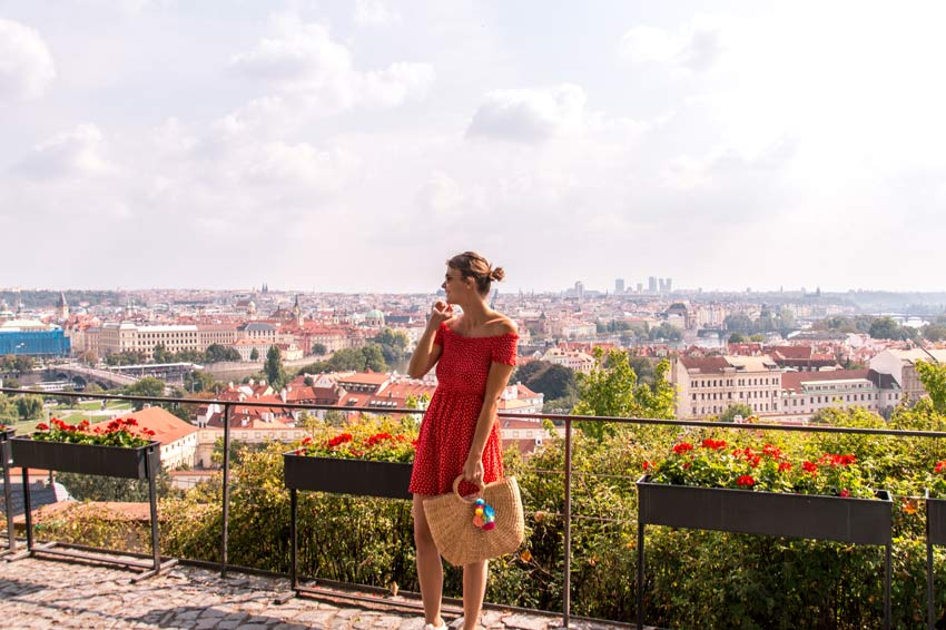 woman in red dress in front of green grass with a view on Prague